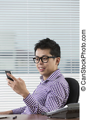 Asian businessman reading his smartphone. - Happy Chinese...