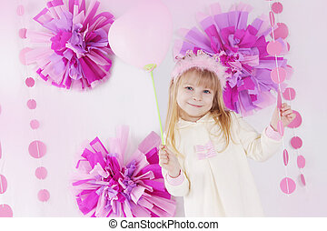 Little girl at pink decorated birthday party with balloon