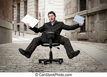 Happy crazy business man rolling downhill on chair with...