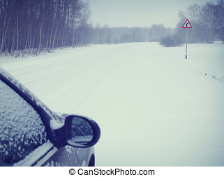Car on a snowy road (focus on the road sign)