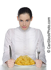 Woman with cutlery bent over a plate of pasta - Young woman...