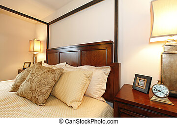 High posts bed with a beautiful beige bedding and nightstand...
