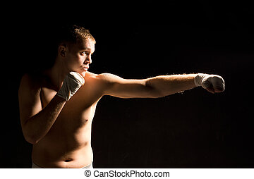 Determined young boxer throwing a punch during training or a...