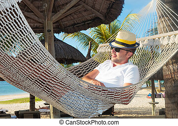relaxed man in a hammock on the beach