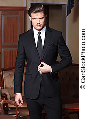 young business man with hand on jacket - photo of a young...