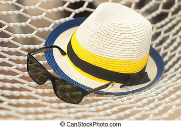 straw hat and sunglasses on a hammock - closeup picture of a...