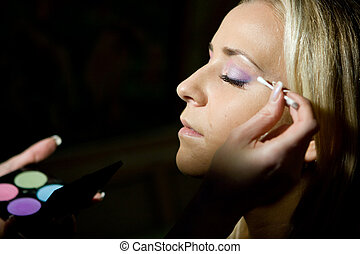 Make-up specialist working on a blond girl