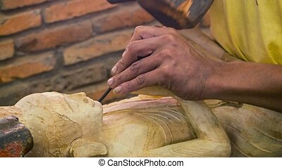 Cambodia, Siem Reap. Carving Buddha statue from a wood -...