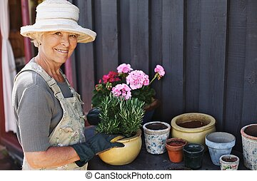 Senior woman planting flowers in a pot - Active senior woman...