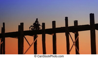 Man with bicycle at old bridge. Burma, Mandalay - Video...
