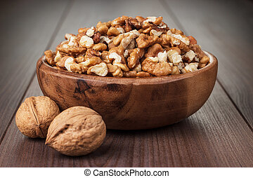 walnuts in the brown wooden bowl on table