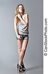 Studio fashion shot: beautiful girl wearing denim shorts and...