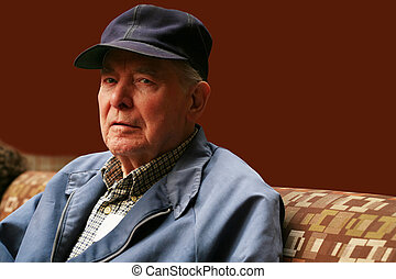 Elderly man sitting in waiting room with serious expression
