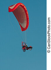 red paraglider on the clear blue sky
