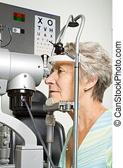 Lady having eye test examination - An older lady taking an...