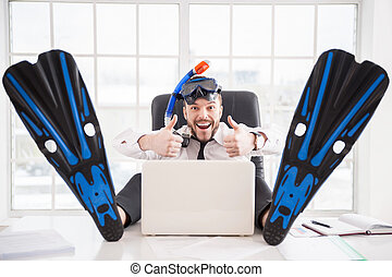 Ready for vacation. Handsome young office worker in in snorkel and flippers gesturing and smiling while sitting at his working place