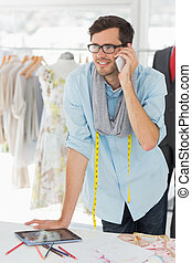 Smiling male fashion designer using mobile phone