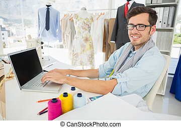 Male fashion designer using laptop
