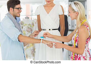 Fashion designers adjusting dress on model - Two fashion...
