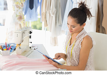 Female fashion designer using digital tablet in studio -...