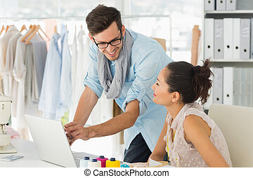Fashion designers using laptop in studio - Male and female...