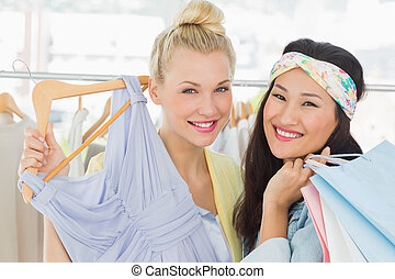 Young women shopping in clothes store - Portrait of two...