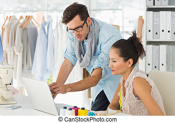 Fashion designers using laptop in s - Male and female...
