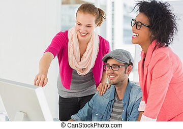 Three cheerful artists working on computer