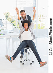 Playful young man pushing woman on chair in office -...