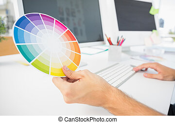 Hand holding color wheel while using computer - Closeup of...