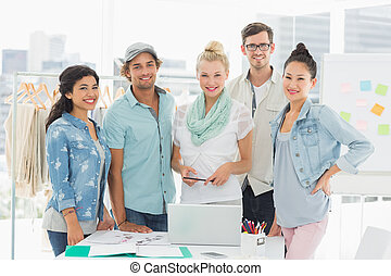 Fashion designers using laptop - Group of fashion designers...