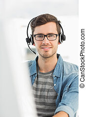 Portrait of a smiling man with headset using computer