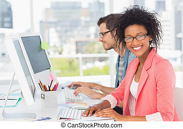 Casual young couple working on computers in office - Smiling...