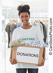 Smiling young woman with clothes donation - Portrait of a...