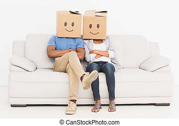 Young couple with happy smiley boxes over faces while...