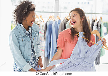 Happy women shopping in clothes sto - Two happy young women...