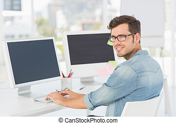 Side view portrait of a male artist using computer in the...