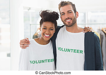Portrait of two young volunteers with arms around standing...