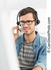 Smiling casual young man with headset using computer in a...