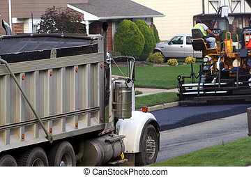 Road Refinishing - Truck and a trailer working on new tar...