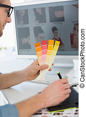 Handsome designer working with digitizer holding colour chart at his desk in creative office