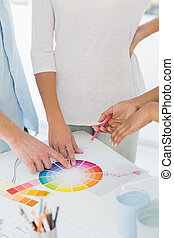 Interior designer showing colour wheel to two customers in...
