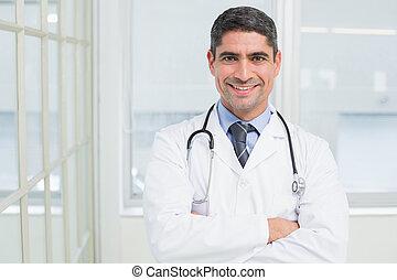 sonriente, macho, doctor, brazos, cruzado, hospital