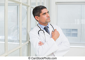 Thoughtful male doctor looking away in hospital - Side view...
