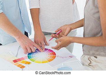 Interior designer showing colour wheel to customers in her...