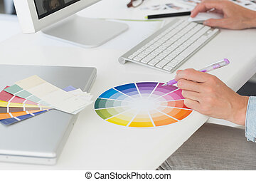 Designer working at her desk using a colour wheel in...