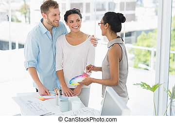 Interior designer showing colour wheel to happy young...