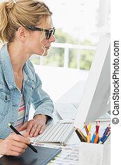Blonde focused designer using digitizer at her desk in...