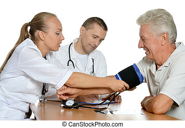 Young nurse measuring blood pressure to the senior woman