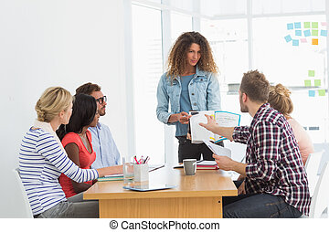 Woman presenting ideas to young designers having a meeting...